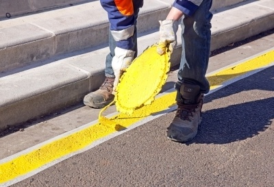 man pouring a yellow paint strip on a road. journey level experience is required to get the C-32 license