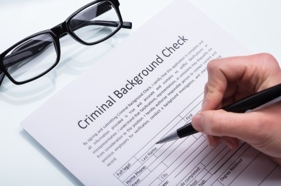 A hand holding a black pen filling out a criminal background check
