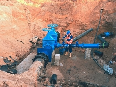 A man working in an excavated area on a pipeline
