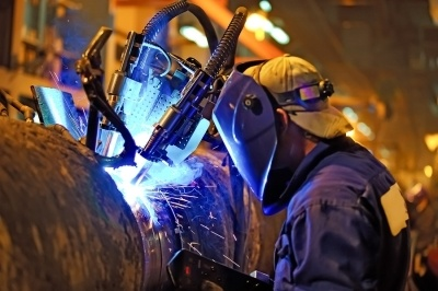 Construction worker wearing a protective mask welding a pipeline. The state board may request to see documentation of your experience before you can take the C-34 license exam