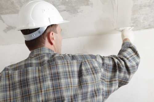 Construction worker wearing a white hard hat, plastering a way