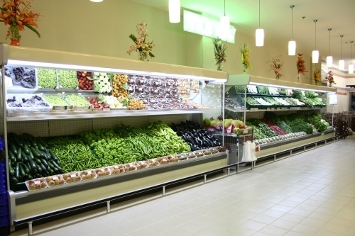 a supermarket refrigeration unit stocked with vegatables