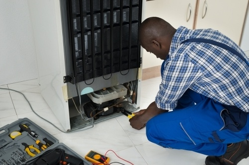 a black male refrigerator contractor fixing a refrigerator