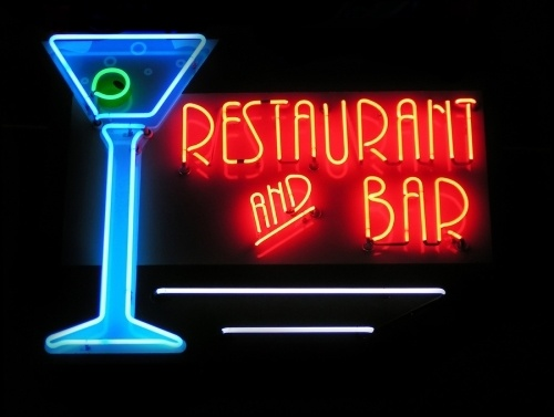 night time view of A neon sign commonly found on a bar. Neon sign says restaurant and bar and has a blue martini glass and green olive