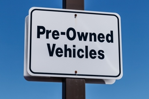 A white rectangular sign with the words pre owned vehicles written in black, bolted to a wooden pole. To get the c-45 license the state board may request to see documentation of your experience building electrical and non electrical signage