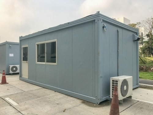 A blue modular home with one door and two windows and an Air conditioning unit connected to the back