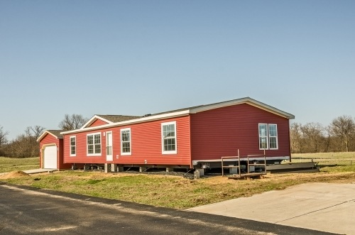 A long red modular with wheels at the bottom, sitting on a plot of land. there are seven windows and a white door.