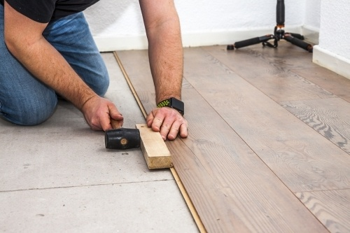 a man kneeled down wearing blue jeans and a black watch using a hammer and a piece of wood to straighten a floor board. In the process of doing a floor installation