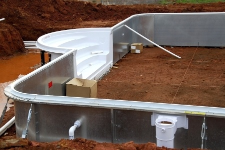 A metal swimming pool frame being installed on top of the ground