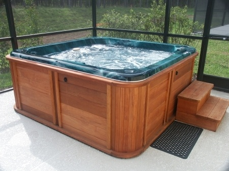 A full hot tub with a wooden exterior and green interior