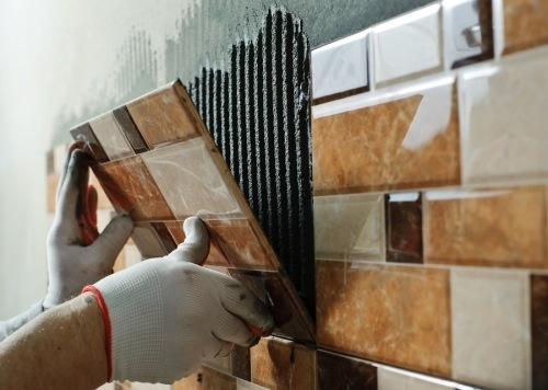 a construction worker wearing white gloves placing a brown tile against a wall