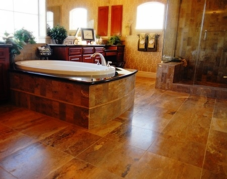 A luxurious bathroom with brown tile floors and jacuzzi
