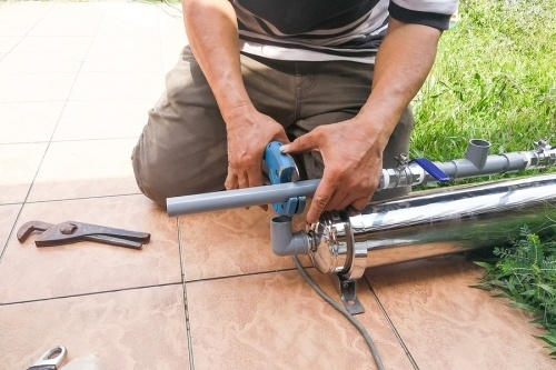 A water conditioning contractor fixing a pvc water filtration pipe outside