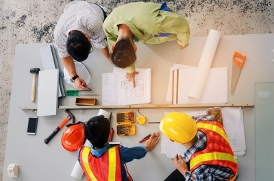 Four construction workers analyzing a construction blueprint, with several tools, pencils and rulers on the table