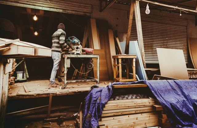 Men using a saw at large woodworking shop