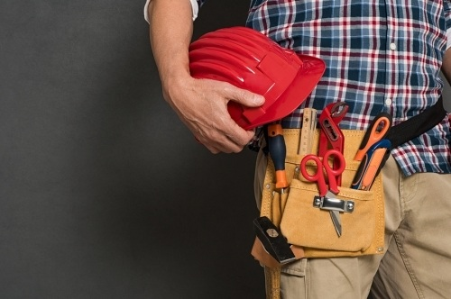 A construction worker wearing a gold tool belt with several tools inside. Also he is holding a red hard hat, wearing a blue checkered shirt