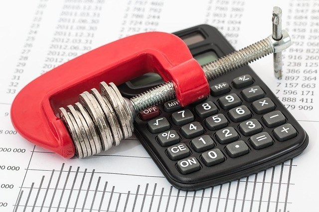 A wrench and calculator on top of a piece of paper. studying for your contractor license exam will greatly increase your chances of passing the concrete services license exam
