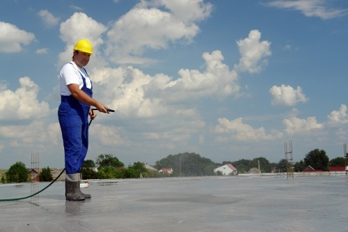 A construction worker wearing blue overalls and a yellow hard hat spraying concrete during the curing process. Concrete services typically entail a wide range of duties
