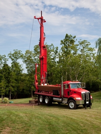 A red truck with a large drill attached at the back, penetrating the earth in a large pasteur