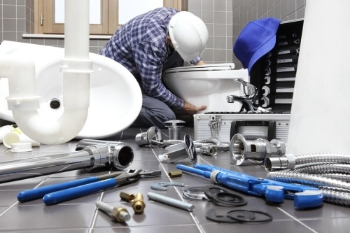 Man wearing a white hard hat fixing a toilet