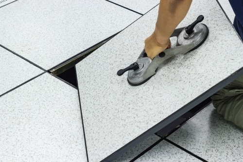 Getting a raised access flooring contractor license requires that you have atleast 4 years journey level experience. a construction worker lifting up a large tile to access a raised floor system