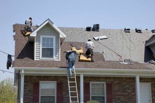 Men working during the day on a roof. One is climbing up the later with a bag of material on his back