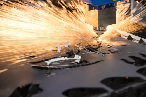 A laser cutting machine cutting a large piece of metal creating alot of sparks