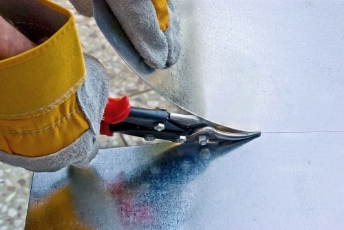 A construction worker wearing protective gloves cutting a piece of sheet metal with scissors
