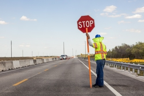Construction worker with stop sign directing traffic around a construction site