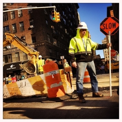 man holding a traffic sign that says slow on the road in front of a jobsite