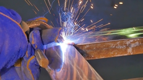 A contractor welding two large pieces of steel together. Purple sparks emanating from the steel