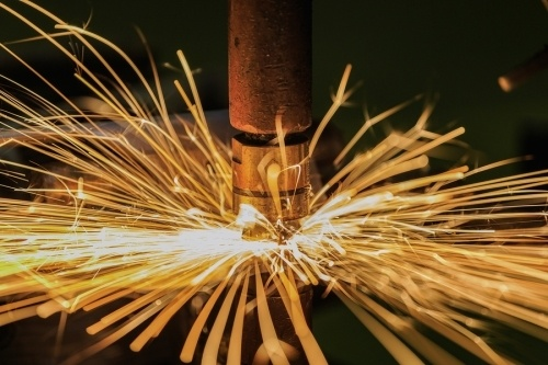 Sparks emanating from an arc cutting a large piece of steel