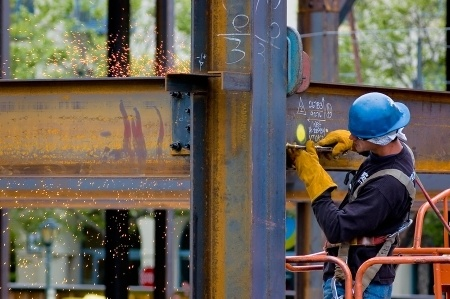 A construction worker welding two large pieces of steel. Journey level experience is required for anyone looking to get the welding license in california