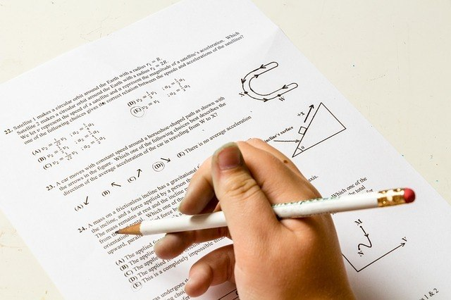 A white hand holding a pencil above a piece of paper with various math problems on it