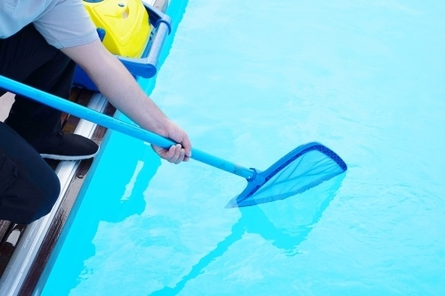 A pool and spa maintenance person using a net attached to a stick to collect debris from a swimming pool