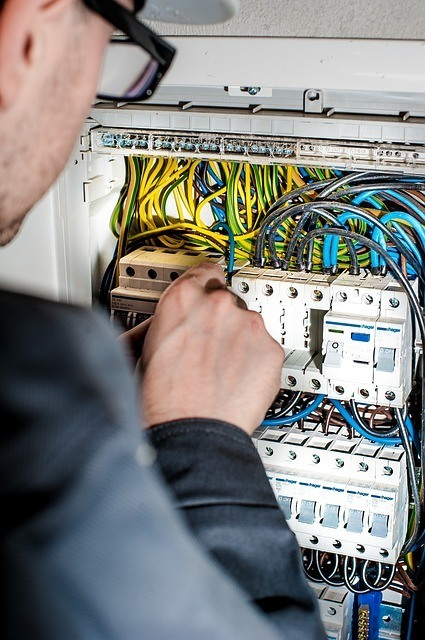 An electrical contractor adjusting wires within a circuit box. The electrical certification is required of any electrician working under a C-10 electrical contractor