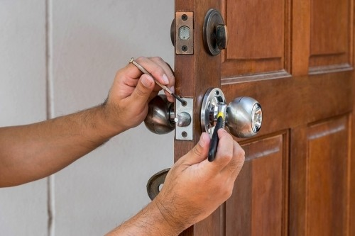 A locksmith fixing a lock and door knob. The D-16 license is for locksmith businesses looking to contract over $500 for their services