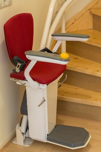 A home handicap chair lift connected to a wooden stair case