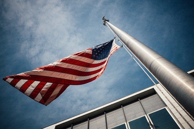 A flag pole with an american flag facing up