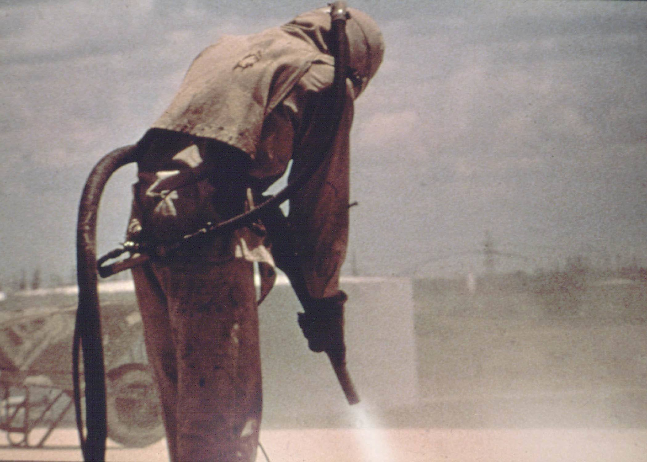 a sandblasting contractor working wearing full protective gear