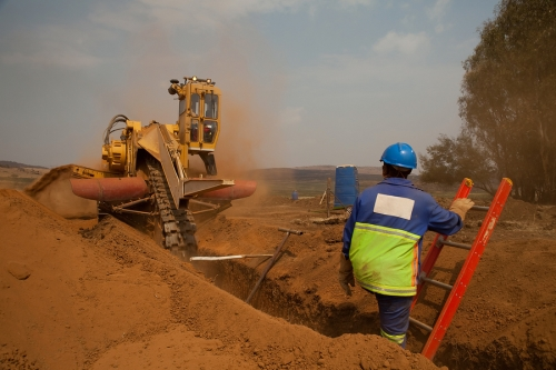 A contractor in front of a trench drilling machine