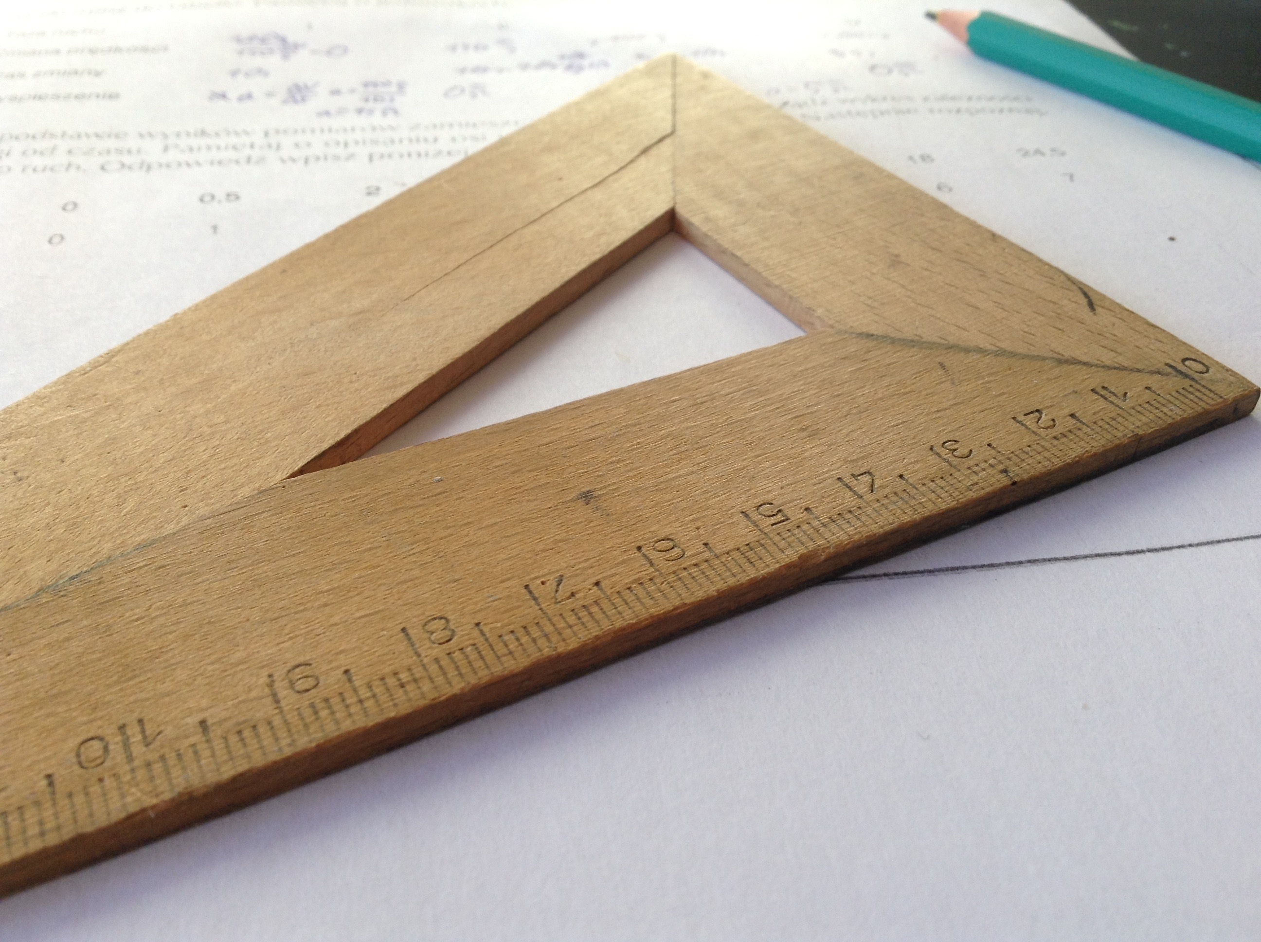 A wooden triangular ruler and turquoise pencil laying on top of a white piece of paper