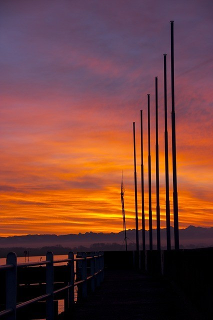 Six poles embedded into the ground with a sunset in the background