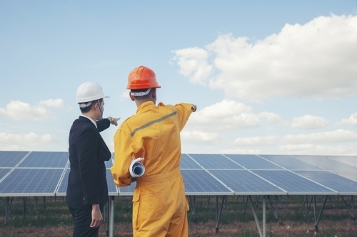 two contractors wearing hard hats pointing out into the distance with a large solar panel in front.