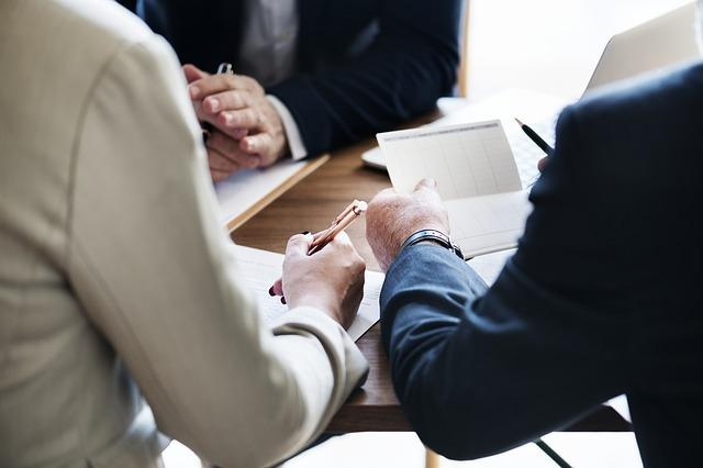 Three business people wearing suits examining documents at a desk. Construction accounting has many moving parts and it is important that you have someone who is familiar with the construction business