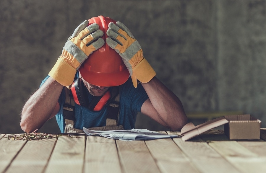 A frustrated white male contractor wearing an orange hard hat looking down at several documents on a table. Bookkeepers play an important role within construction accounting as they organize all of the day to day documents