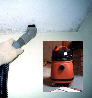 A shop vacuum and person using a hand vacuum to dry out a wall of moisture