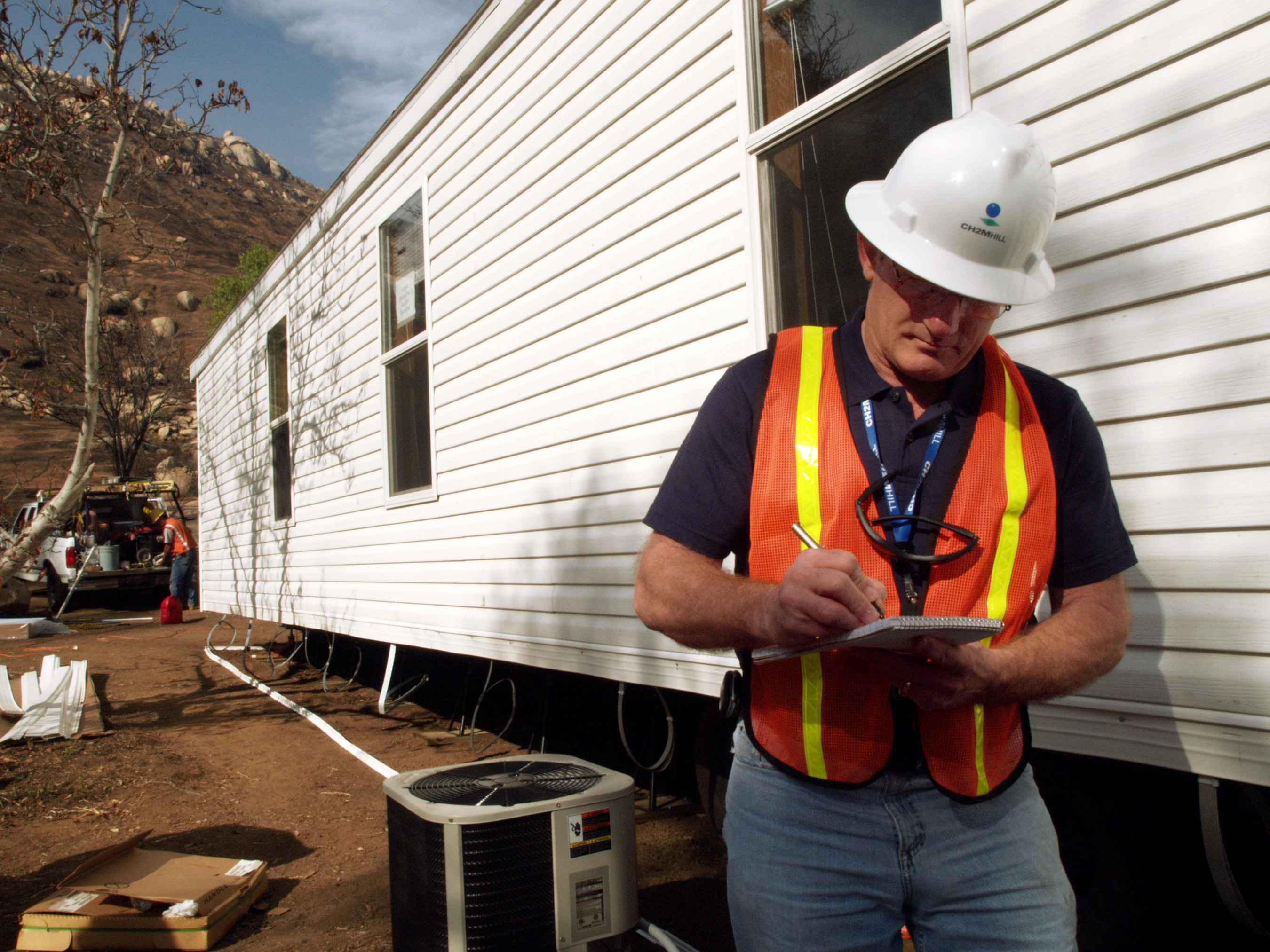 Image features a white man wearing a hard hat with construction vest. holding a clip board infront of a mobile home. Professional home inspectors check for major issues with residential homes