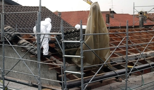 Two contractors on a roof removing asbestos from a roof