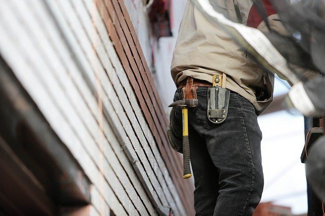 A general contractor wearing a tool belt with a yellow hammer hanging from the side. General Contractor must meet strict requirements. they are licensed, bonded and often hold workers compensation and liability insurance